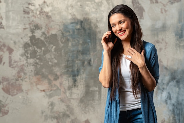 Glimlachende gelukkige vrouw die op smartphone tegen een abstracte achtergrond spreken.