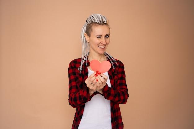Glimlachende gelukkige vrouw die rood document hart houdt