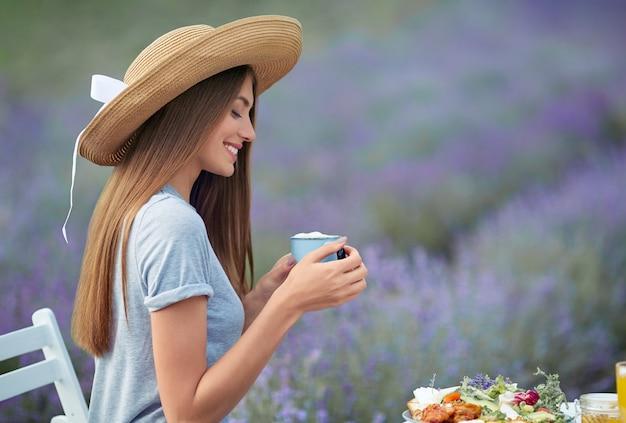 Glimlachende gelukkige vrouw die thee drinkt in lavendelveld
