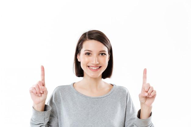 Glimlachende gelukkige vrouw die twee vingers benadrukt op exemplaarruimte