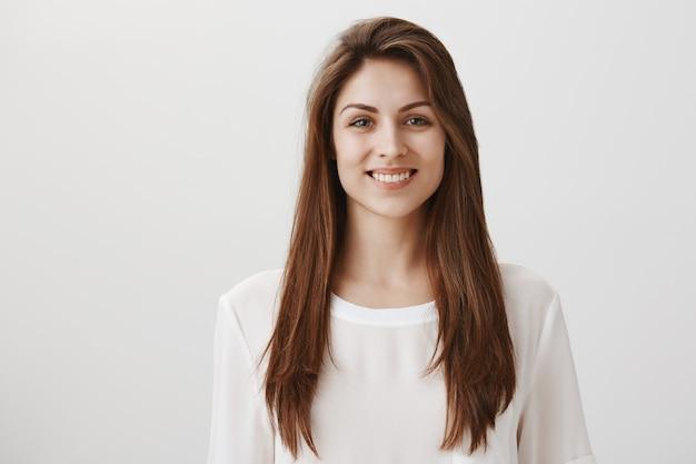 Glimlachende gelukkige vrouw die zich in wit casual t-shirt op grijs bevindt
