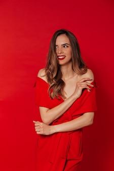 Glimlachende gelukkige vrouw in rode kleding met rode lippen die over rode muur stellen