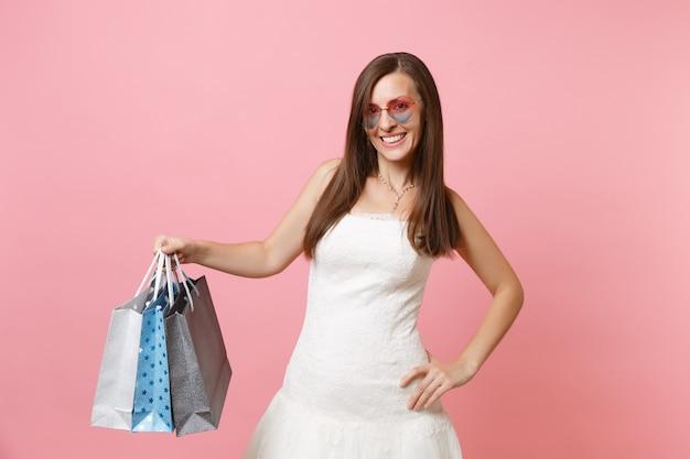 Glimlachende gelukkige vrouw in witte jurk en hartbril met veelkleurige pakketten met aankopen na het winkelen