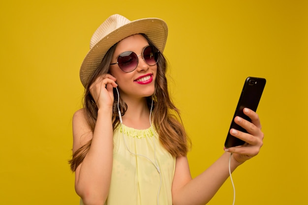 Glimlachende gelukkige vrouw in zomerhoed en zonnebril met smartphone