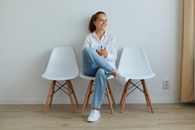 Glimlachende gelukkige vrouw met brede glimlach, smartphone in handen houden, camera kijken, op stoel zitten, jeans en wit overhemd dragen, positieve emoties uiten,