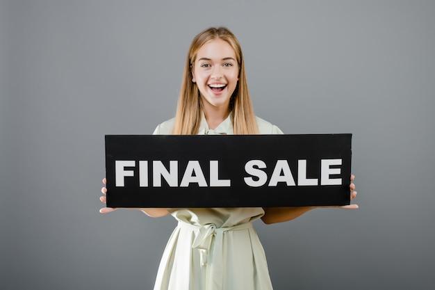Glimlachende gelukkige vrouw met definitief die verkoopteken over grijs wordt geïsoleerd