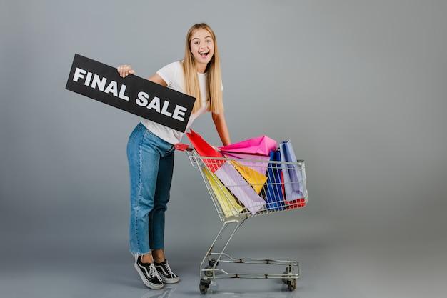 Glimlachende gelukkige vrouw met definitief verkoopteken en handkar met kleurrijke die het winkelen zakken over grijs worden geïsoleerd
