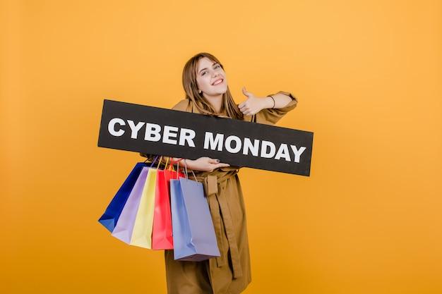 Glimlachende gelukkige vrouw met het teken van de cybermaandag en kleurrijke die het winkelen zakken over geel wordt geïsoleerd