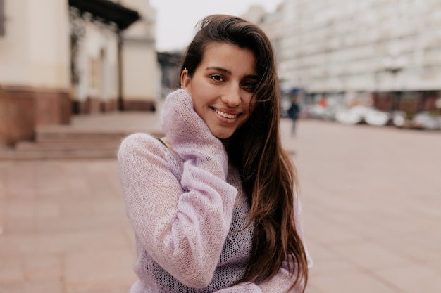 Glimlachende gelukkige vrouw met lang haar die violette sweater dragen die over oude gebouwen stellen