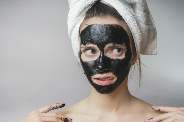 Glimlachende gelukkige vrouw paste huidverzorging zwarte mack toe op face.moisturizer
