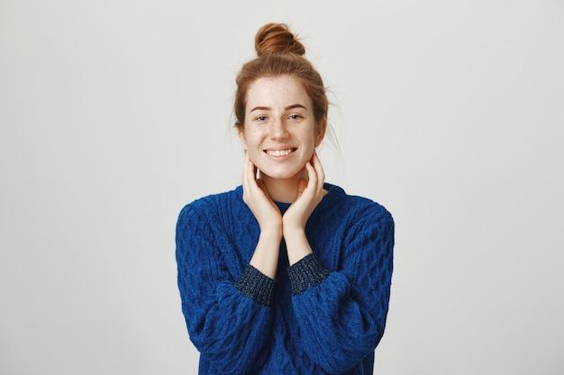 Glimlachende gelukkige vrouwelijke student met rood haar wat betreft hals