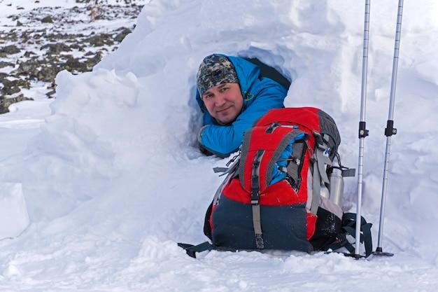 Glimlachende gelukkige wandelaar die in de winter uit een kleine besneeuwde hut-iglo gluurt naast een liggende rugzak