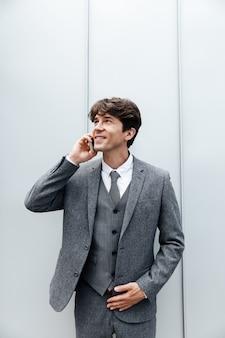 Glimlachende gelukkige zakenman in kostuum dat een mobiel telefoongesprek heeft