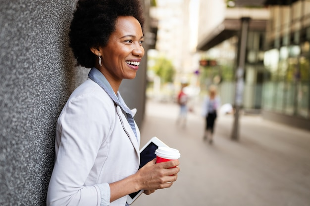 Glimlachende gelukkige zakenvrouw, advocaat wandelen met koffie in de stad