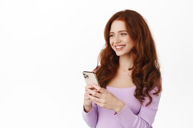 Glimlachende gembervrouw die smartphone op wit houdt