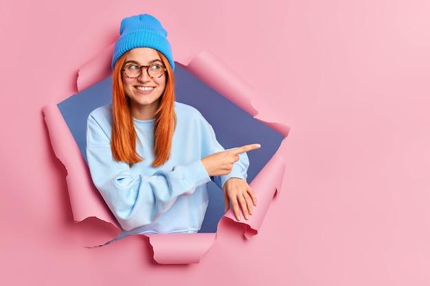 Glimlachende gembervrouw voelt zich optimistisch wijzend op kopie ruimte, draagt blauwe hoed bril en trui breekt door papier