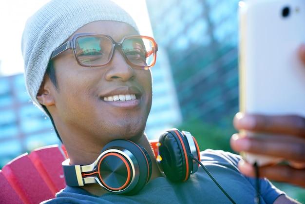 Glimlachende gemengde gerende kerel die hoofdtelefoon buiten in park met behulp van