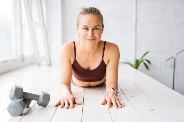 Glimlachende geschikte jonge vrouw met perfect atletisch lichaam die yogaoefeningen doet die bij vensterbank liggen