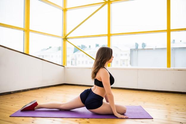 Glimlachende geschikte vrouw die yogaoefeningen met haar lichaam van de vloer opgeheven uitoefenen
