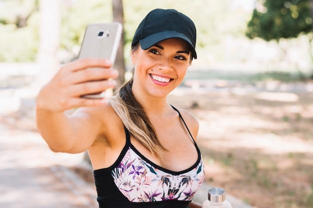Glimlachende geschiktheids jonge vrouw die selfie uit cellphone nemen