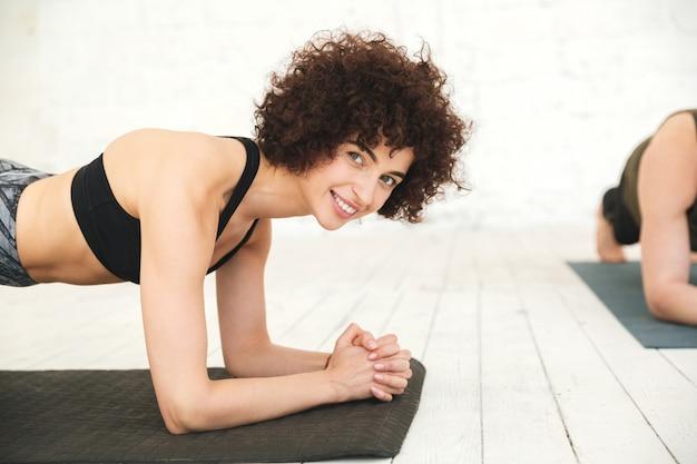 Glimlachende geschiktheidsvrouw die op een oefeningsmat planking