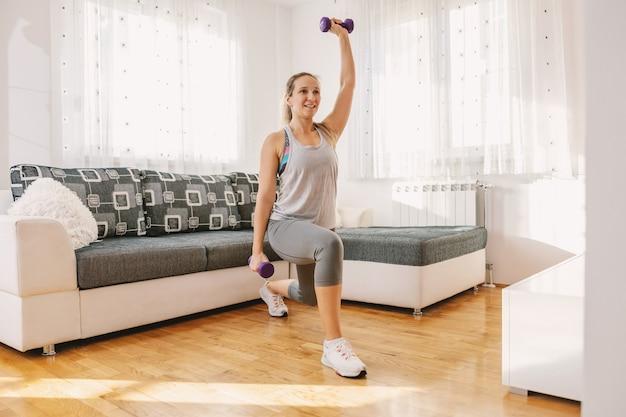 Glimlachende gespierde sportvrouw in vorm die lunges doet terwijl hij halters vasthoudt.