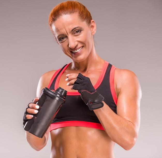 Glimlachende gespierde vrouw met sportvoeding.