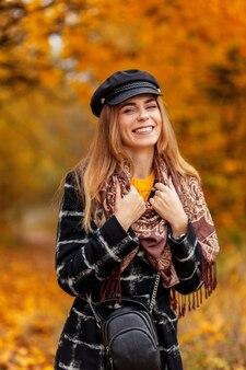 Glimlachende gezonde vrouw in stijlvolle blauwe sportkleding met moderne draadloze koptelefoon jogger in bos bij zonsondergang. sportief meisje met aantrekkelijke glimlach met sexy lichaam dat buiten op zomerdag loopt.