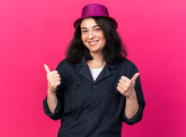 Glimlachende glimlachende jonge blanke feestvrouw met een feesthoed die naar de voorkant kijkt en duimen laat zien die op een roze muur is geïsoleerd
