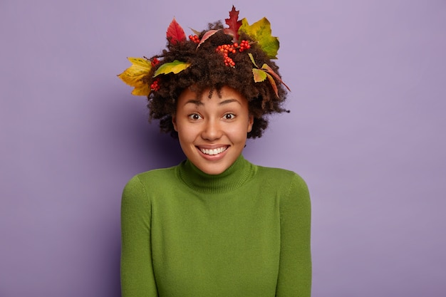 Glimlachende, goed uitziende, krullende vrouw die in een hoge geest is, kijkt gelukkig naar de camera, draagt een groene coltrui, herfst gevallen bladeren op het hoofd, geïsoleerd op paarse muur