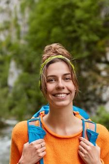 Glimlachende goed uitziende vrouw reiziger in oranje trui, draagt rugzak, draagt hoofdband