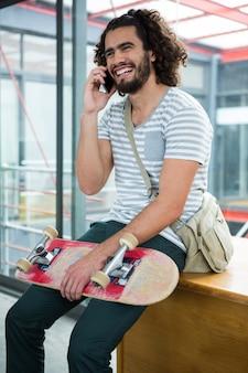 Glimlachende grafisch ontwerper die op mobiele telefoon spreekt