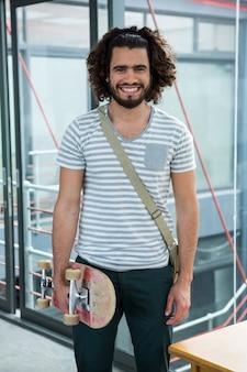 Glimlachende grafisch ontwerper met skateboard dat zich in creatief bureau bevindt