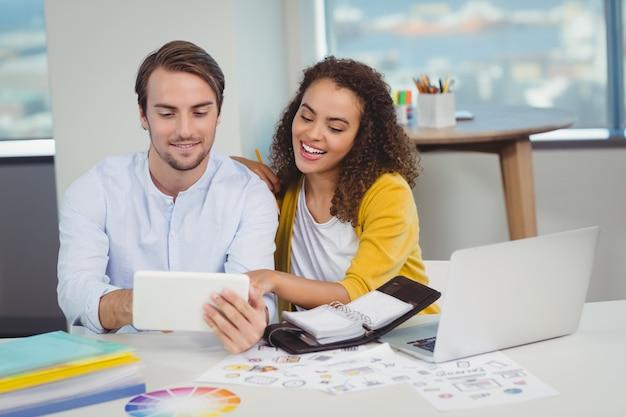 Glimlachende grafisch ontwerpers die aan tafel zitten en digitale tablet gebruiken