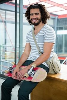 Glimlachende grafisch ontwerperzitting met skateboard in creatief bureau