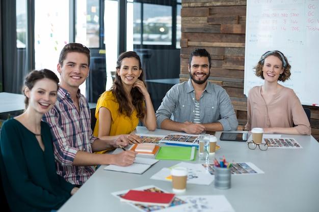 Glimlachende grafische ontwerpers die in bureau zitten