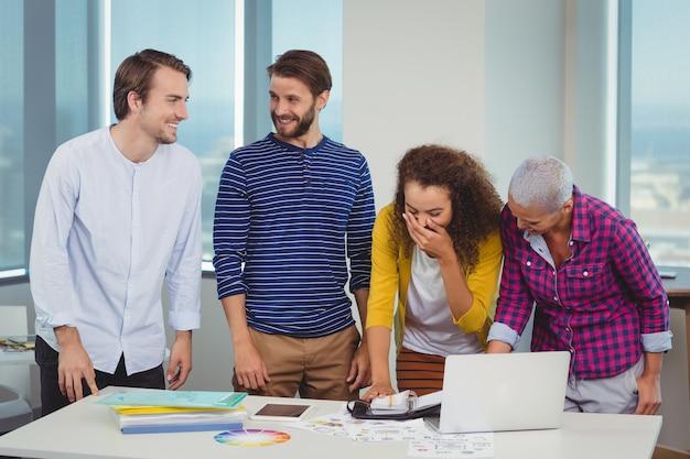 Glimlachende grafische ontwerpers die met elkaar in wisselwerking staan