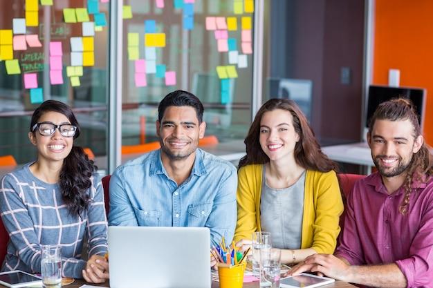 Glimlachende grafische ontwerpers die over laptop in vergadering bespreken
