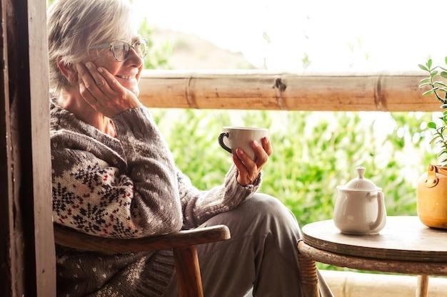 Glimlachende grijsharige senior vrouw in een wintertrui zittend op het houten balkon wegkijkend met een kopje thee.