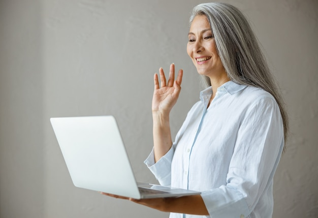 Glimlachende grijsharige volwassen aziatische zakenvrouw zwaait hand naar collega's bij videocall via moderne laptop poseren in de buurt van grijze stenen muur in studio