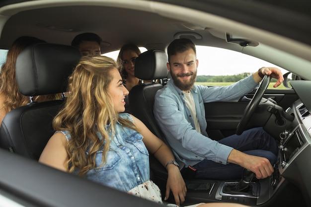 Glimlachende groep vrienden die in auto reizen