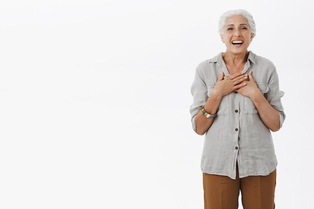 Glimlachende grootmoeder die dankbaar keek, haar borst blij aanraakte