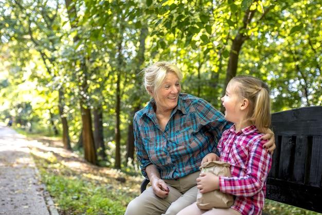 Glimlachende grootmoeder die haar vrouwelijke kleinkind in het park koestert