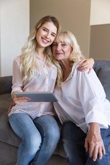 Glimlachende grootmoeder en haar kleindochter die een tablet houden