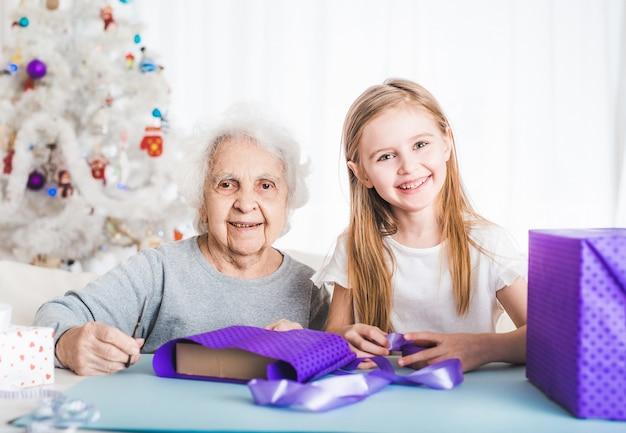 Glimlachende grootmoeder met kleine kleindochter bedekken cadeaus met decoratief papier