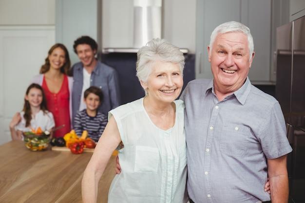 Glimlachende grootouders met familie in keuken