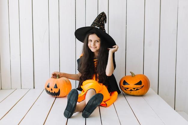 Glimlachende halloween-heks met pompoenen