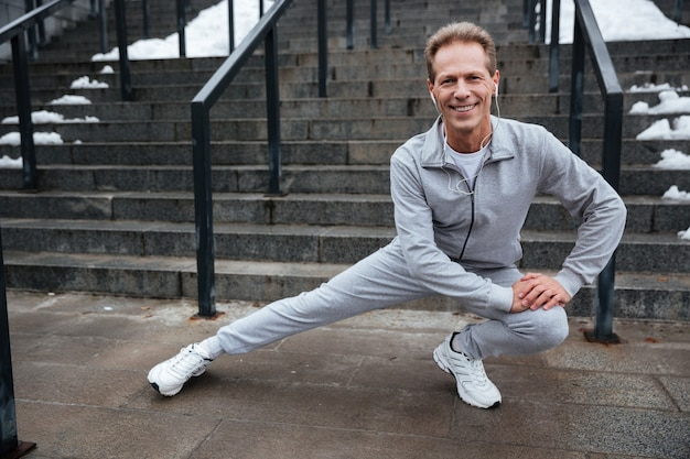 Glimlachende hardloper in grijze sportkleding die zich bij de trap opwarmt en naar de camera kijkt