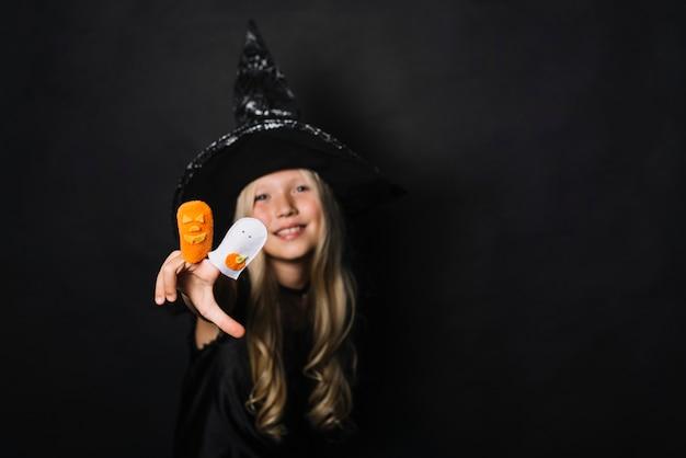 Glimlachende heks die halloween-speelgoed toont