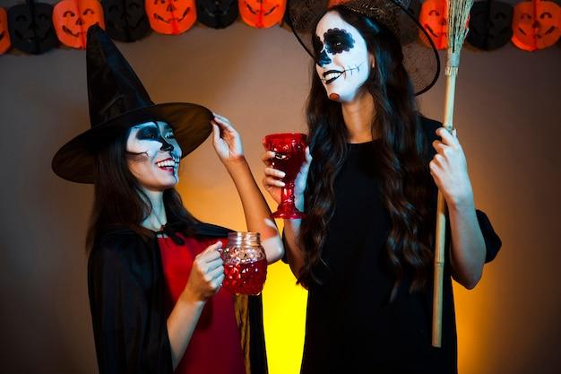 Glimlachende heksen met drankjes op een feestje